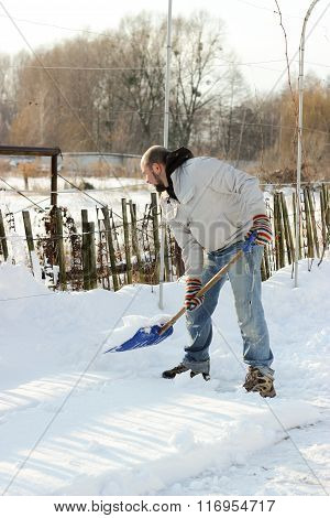 Man Cleans The Track From Snow Shoveling, Sunny Winter Day