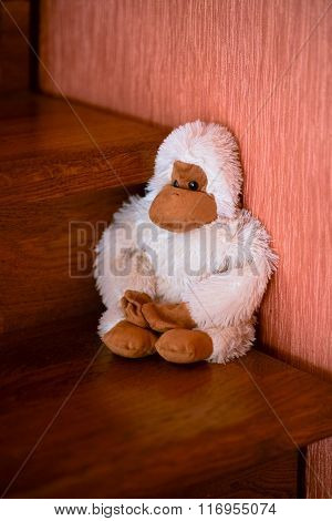 handmade white monkey toy seating on the brown wood stairs