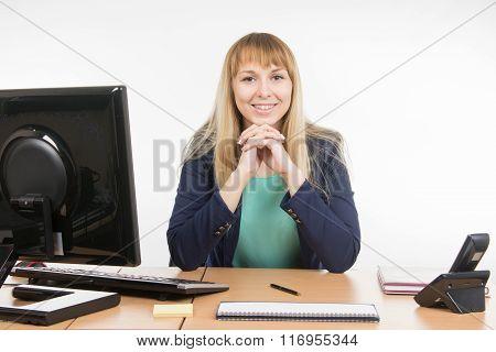 Happy Secretary Sitting Behind A Desk