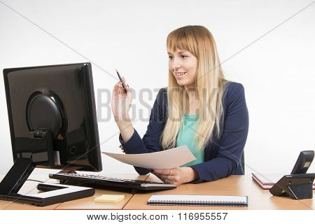 Happy Business Woman Working At A Computer And Holding A Piece Of Paper And A Pen