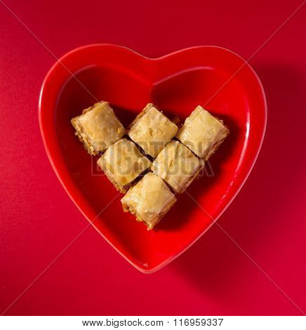 Popular middle eastern dessert - Paklawa in a red heart shaped dish. Unhealthy food concept. View from above.