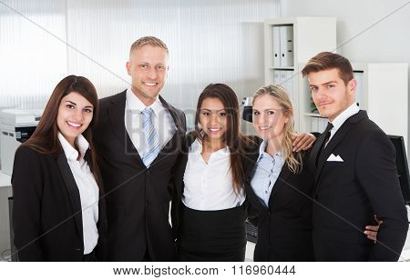 Business People Standing Arms Around In Office