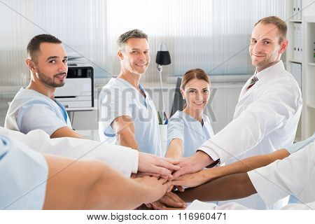 Confident Medical Team Smiling While Joining Hands