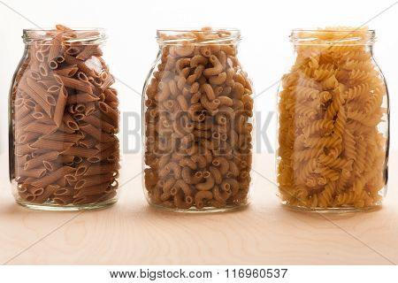 Wheat Buckwheat And Spelt Pasta Separated In Three Glass Jars.