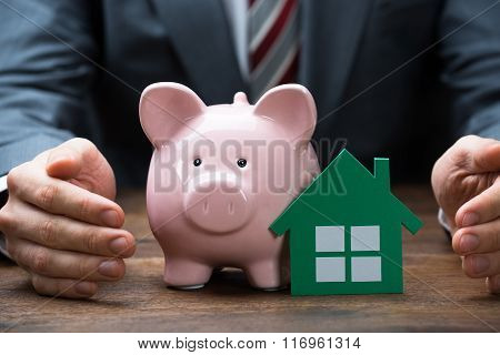 Businessman Protecting Green Paper House And Piggybank