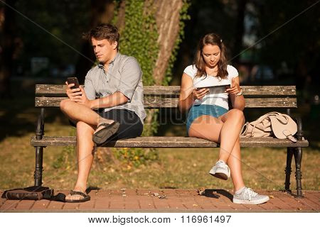 Young Couple Distracted With Communication Technology Tablet And Smart Phone Sitting On A Bench Soci