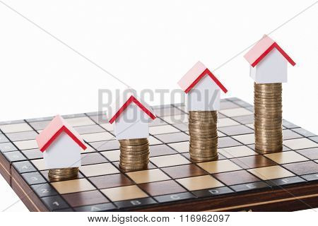 House Models And Stacked Coins On Chessboard