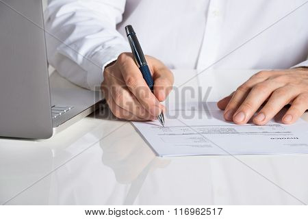 Businessman Analyzing Invoice By Laptop