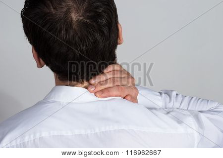 Rear View Of Businessman Suffering From Neckache