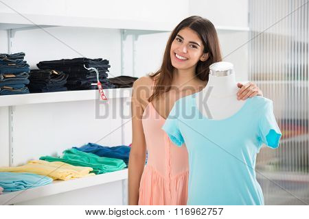 Smiling Woman Standing By Mannequin Displaying Top In Store