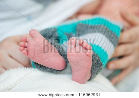 Infant's Small Feet Closeup With Mother Hands