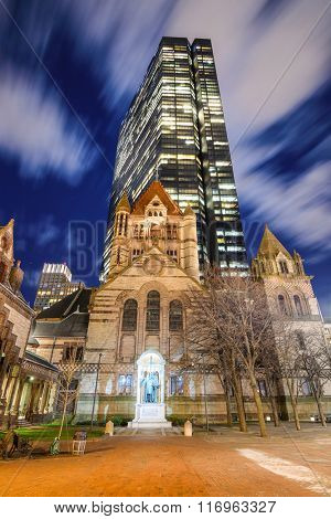 BOSTON, MASSACHUSETTS - APRIL 4, 2012: John Hancock Tower stands over Trinity Church. At 790 feet, it is the tallest building in the New England region.