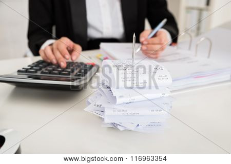 Receipts In Paper Nail With Businesswoman Working At Desk
