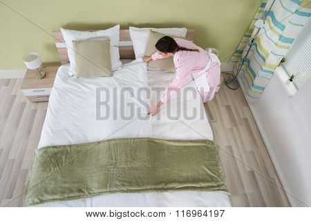 Female Housekeeper Arranging Bedsheet On Bed