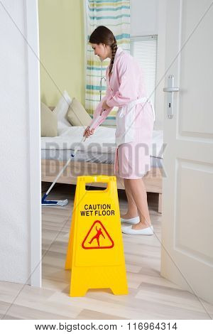Female Housekeeper Cleaning Floor With Mop