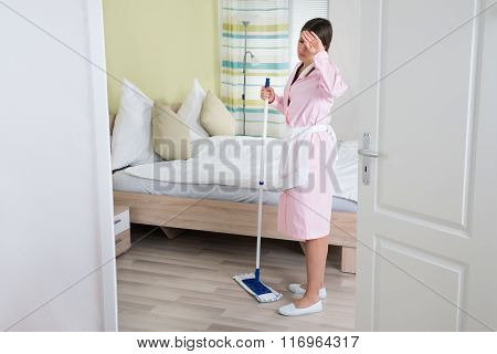 Exhausted Young Housekeeper With Mop