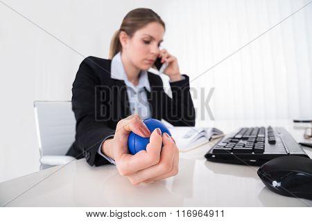 Businesswoman Pressing Stressball At Desk