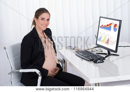 Pregnant Businesswoman Sitting At Desk