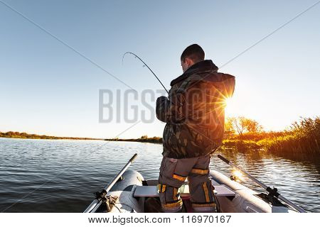 Man fishing from the boat on the autumn lake