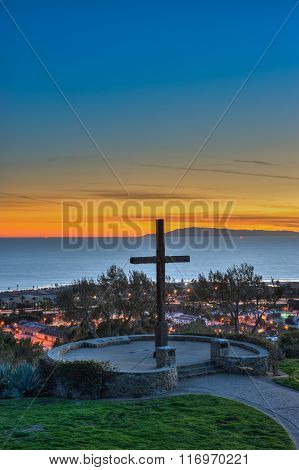 Ventura hillside cross silhouetted against sunset glow.