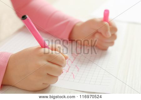 Child drawing with pink felt pen on paper, closeup