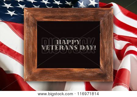 Text Happy Veterans on chalkboard in frame on American flag background