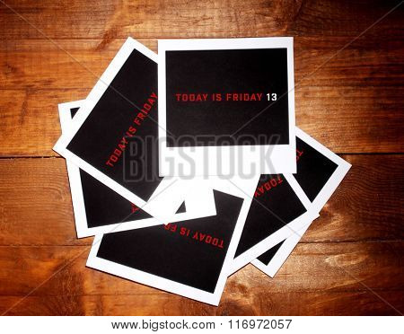 Photo papers with text Today is Friday 13 on wooden background
