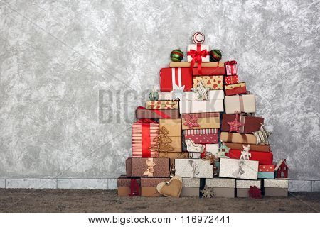 Christmas tree made of present boxes and other decor on the floor