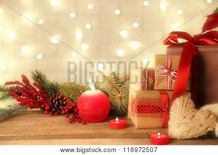 Set of wrapped gifts for Christmas with red candles on brick wall background