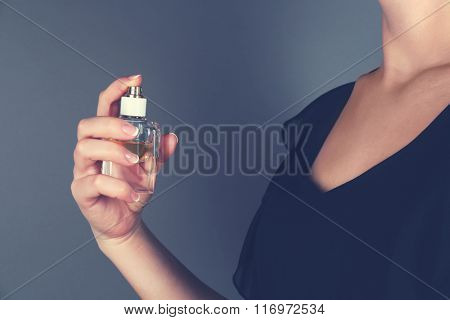 Young woman applying perfume on her neck