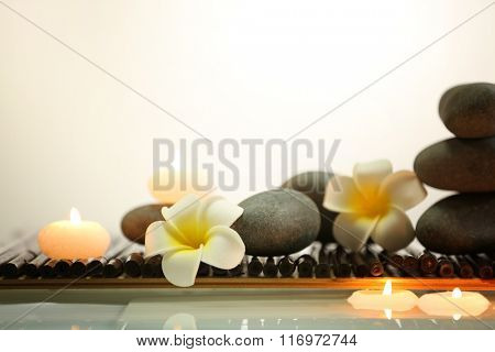 Spa still life with stones, candles and flowers in water on light background