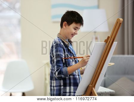 Boy drawing on an easel at home
