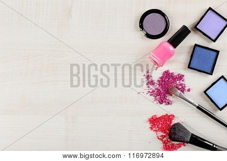 Makeup tools and cosmetics on a wooden background