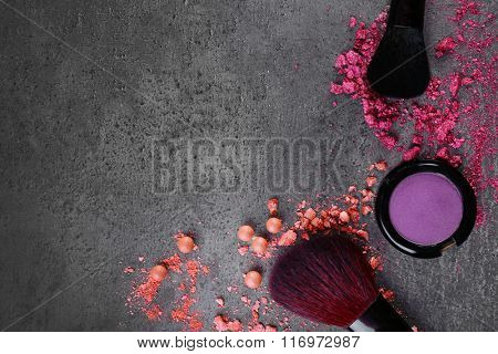 Two makeup brushes with shadows and pink rouges on gray background closeup
