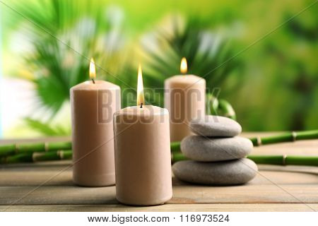 Spa composition of candles, stones and bamboo on blurred background