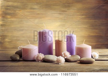 Spa set with candles, pebbles and flowers on wooden background