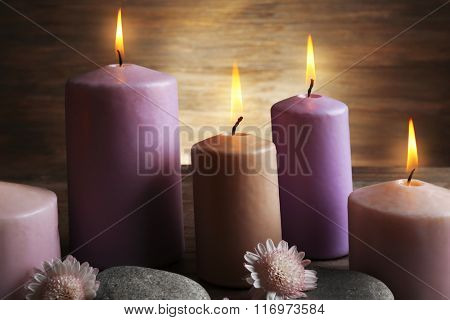 Spa set with candles, pebbles and flowers on wooden background, close up