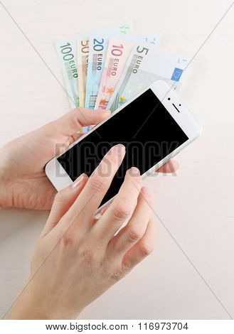 Hands holding smart phone over euro banknotes on light table. Internet earning concept
