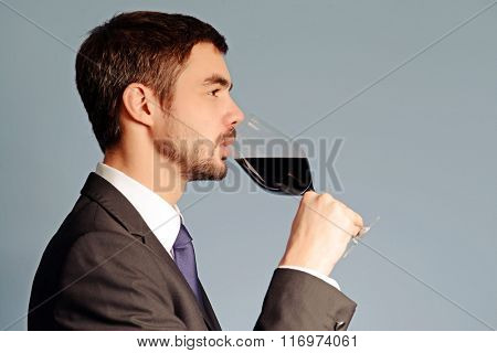Man testing red wine in glass on blue background