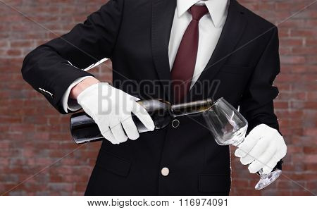 Man in suit pouring red wine into a glass on brick wall background