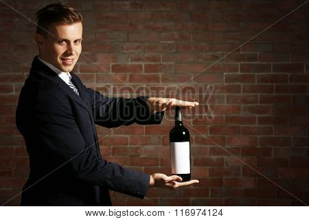 Attractive man holding a bottle of red wine in hands on brick wall background