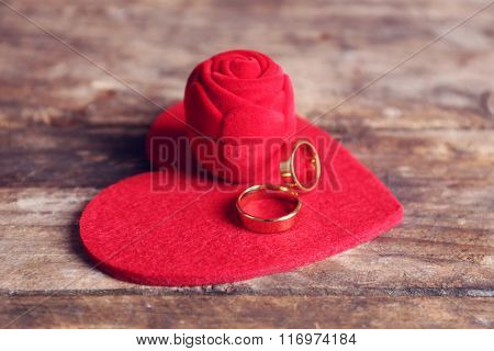 Red velvet silk rose box and weddings rings with heart on wooden background closeup
