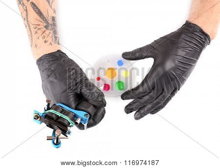 Tattooist hands in black gloves with tattoo machine and colourful inks isolated on white background, close up