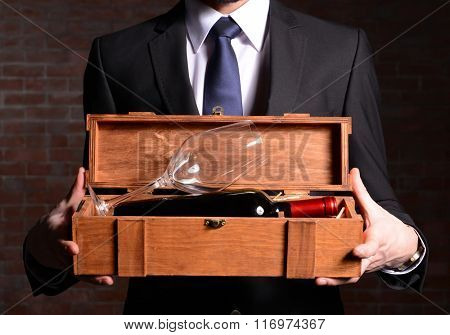 Man holding a bottle of red wine and glass in wooden box on brick wall background