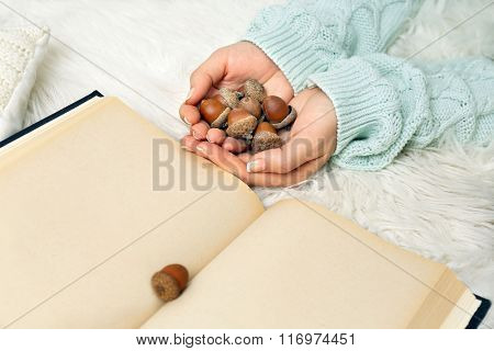Woman holding acorns near book, closeup