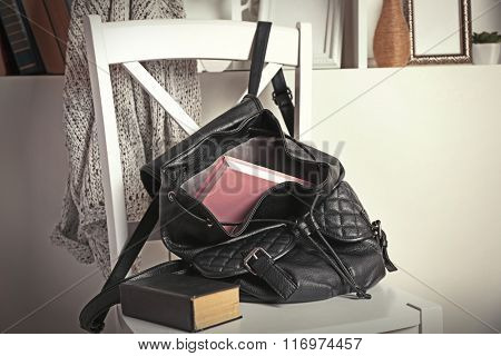 Fashion female backpack with books on white chair