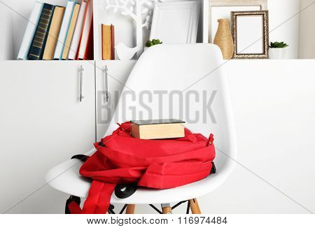 Red backpack with book on white chair