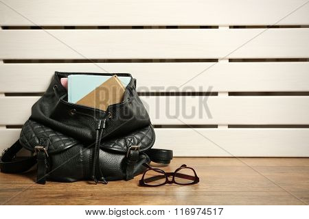 Fashion female backpack with books and glasses on wooden background