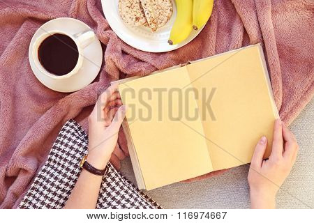 Female hands with open book, plaid, fruits and coffee on sofa. Top view