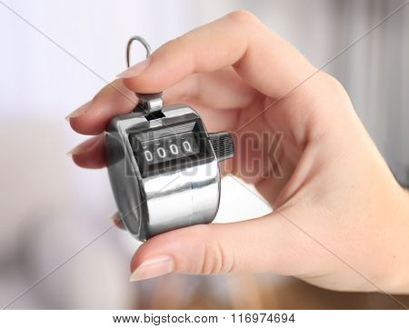 Stopwatch in hand on blurred background, close up